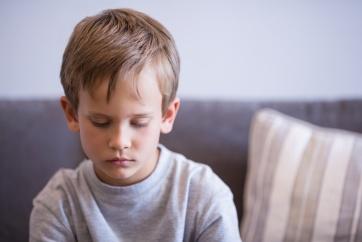 Upset boy sitting on sofa in corridor